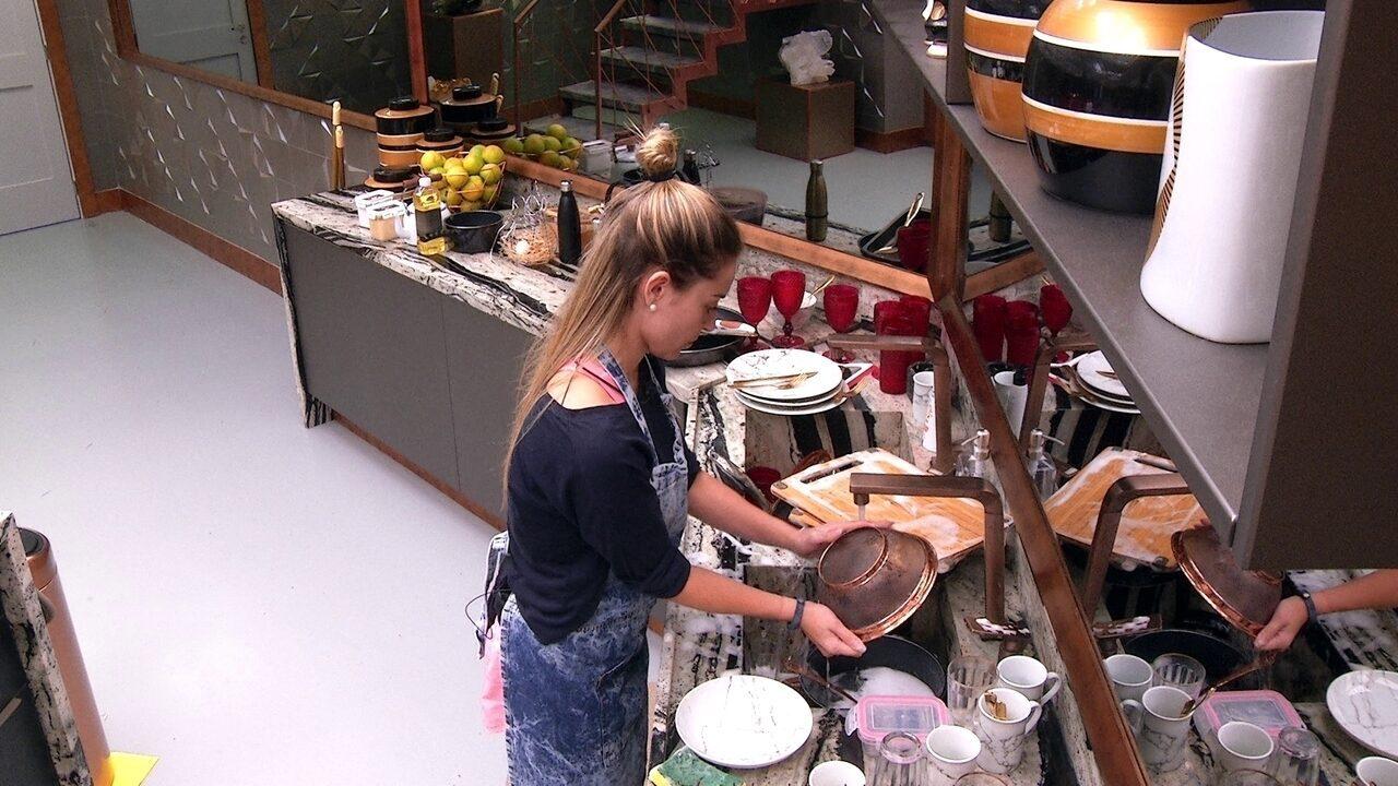 Paula lava a louça sozinha na cozinha