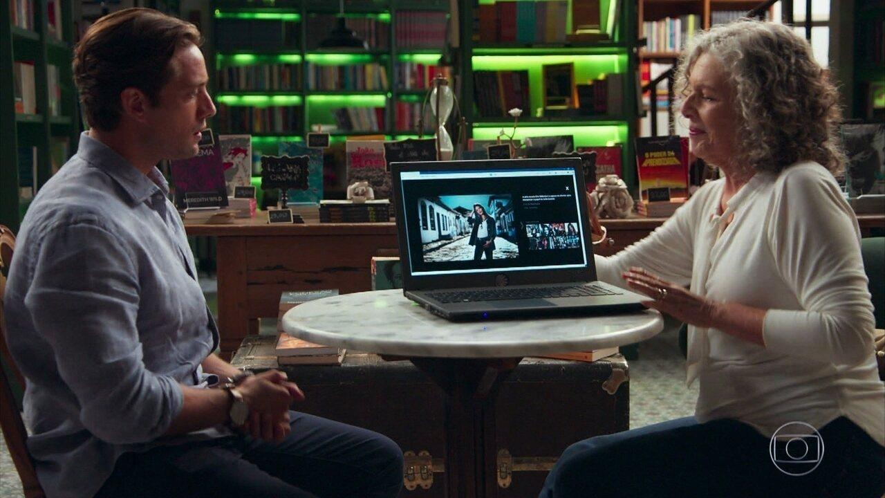 Daniel (Rafael Cardoso) se encanta ao ver as fotos de Cris (Vitória Strada)