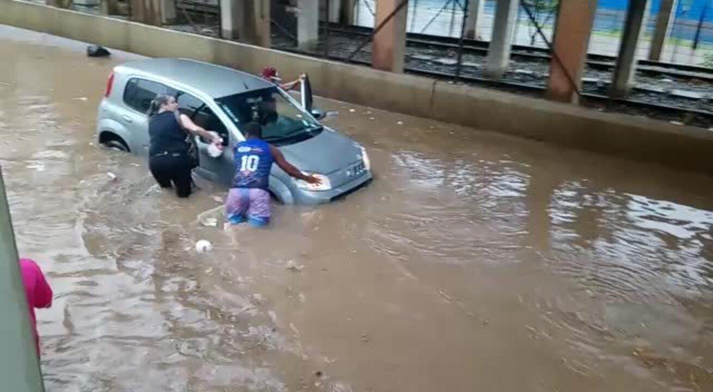 Pessoas ajudando a retirar o carro em que estavam mãe e filho
