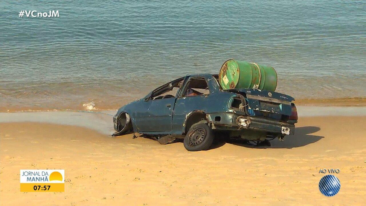 Carro é jogado na areia da praia por homens, em Boa Viagem